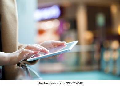 Close-up shot of female hands using touchpad in public place. Defocused interior in background