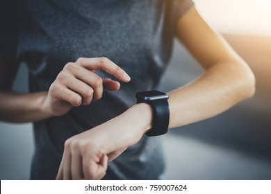 Closeup shot of female jogger hand checking her progress on smartwatch, young athlete woman using smartwatch device for checking her results while training outdoor, flare light effects