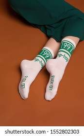 """Close-up shot of female legs in wide green trousers and white socks with green stripes and lettering """"1997, hip-hop, fuck off"""". The photo is made on the brown background."""