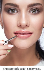 Closeup shot of female paint her lips by cosmetic brush lipstick on lips