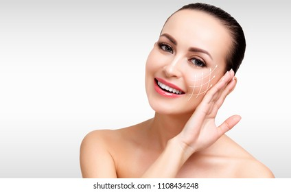 Closeup shot of female pretty face with white arrows on skin for cosmetic medical procedures, grey steel background