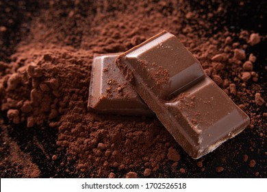 close-up shot of a few ounces of chocolate on cocoa powder. Dark background.