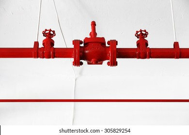 Closeup shot of a fire hydrant pump system consisting of steel pipes painted red against isolated white wall