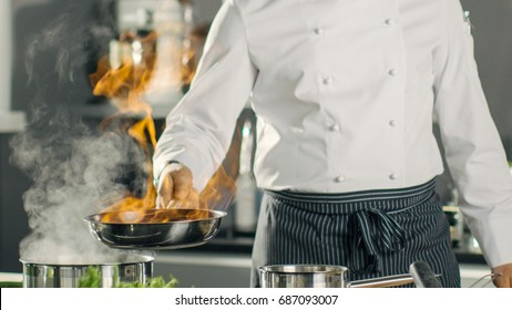 Close-up Shot of Fireing Oil on a Pan. Flambe Style Cooking. Cook Works in a Modern Kitchen with Lots of Ingredients are Around.