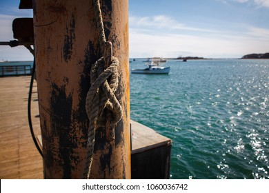 A closeup shot of fishing rope tied to a crane post with a lobster boat moored in Cape Porpoise harbor, Maine.  The rope and crane are used to unload the catch from local fishing boats onto the pier.