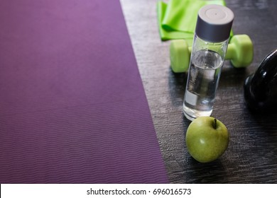 Closeup shot of a fitness gum, bottle of water, an apple and a dumbbell and a kettle bell aside exercise mat on a dark wooden floor background. Have some refreshment when you exercise. Copy space
