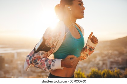 Close-up shot of fitness woman running outdoors. Caucasian female jogging in morning with bright sunlight.