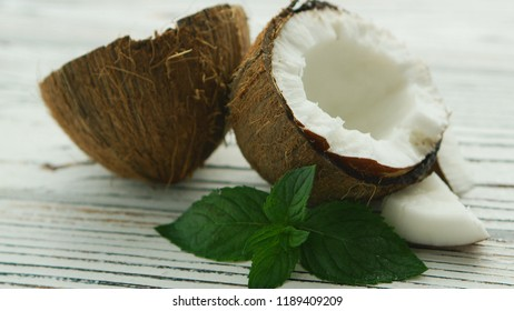 Closeup shot of fresh cut coconut into halves composed on wooden table with green mint leaves