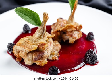 Closeup shot of fried chicken or duck or turkey wings or legs in sweet berry jam with blackberry and peppermint leaves as decoration. Gourmet dish in a luxury restaurant