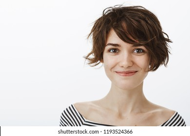 Close-up shot of friendly joyful attractive female with short stylish harcut and cute smile, gazing at camera, talking politely with interesting person, standing satisfied and happy over grey wall