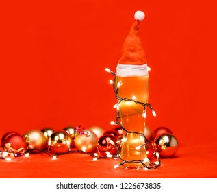 Close-up shot of full pilsner glass of pale lager beer or ale with Santa Claus or christmas red hat on top, wrapped in christmas lights and christmas baubles in background