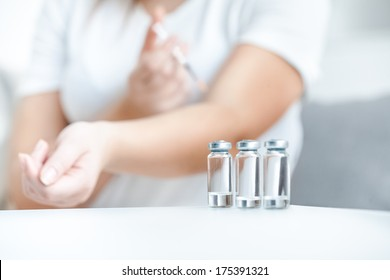 Closeup shot of glass bottles with insulin against woman doing prick