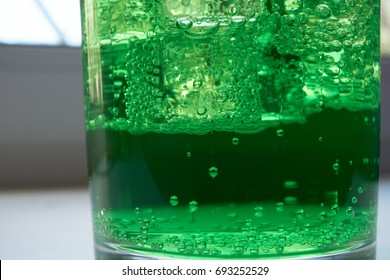closeup shot of a glass filled with green soda aerated water with ice cubes