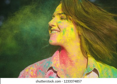 Closeup shot of gorgeous girl with short hair posing with exploding yellow Holi paint in the park. Space for text