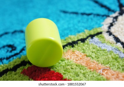 A closeup shot of a green cylinder-shaped toy on carpet