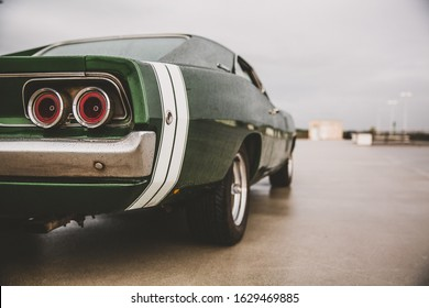 A closeup shot of a green muscle car on a blurred background