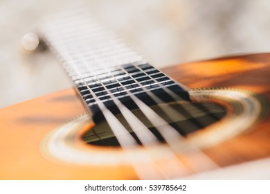 Closeup shot of guitar and strings with very shallow depth of field