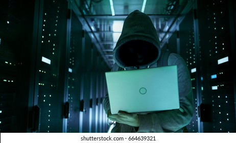 Close-up Shot of a Hacker with Hidden Face in a Hoodie Standing in the Middle of Data Center full of Rack Servers and Hacking it with His Laptop.