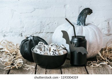 close-up shot of halloween composition with pumpkins, marshmallows and can of soda