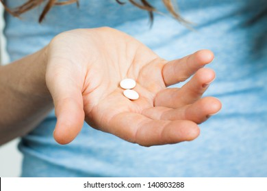 Close-up shot of a hand holding two white pills.