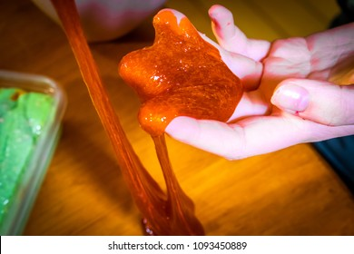 A closeup shot of a child's hand playing with a toy called slime.  Making slime is very popular  among children.