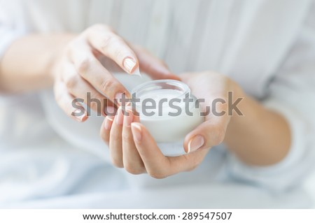 Closeup shot of hands applying moisturizer. Beauty woman holding a glass jar of skin cream. Shallow depth of field with focus on moisturizer.