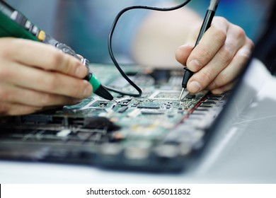 Closeup shot of hands testing electric current in circuit board of disassembled laptop using multimeter tool on table in maintenance shop