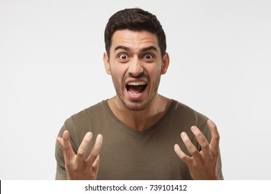 Closeup shot of handsome male standing isolated against grey backgroung and screaming desperately, gesturing with both hands