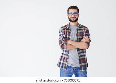 Close-up shot of handsome man in blue glasses standing with arms folded isolated on a white background
