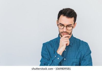 Closeup shot of handsome serious pensive male model in glasses and blue shirt, looking down thinking about problem, holding his chin. People and business concept. Copy space for your advertisement.