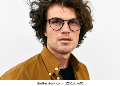Closeup shot of handsome serious young man posing for advertisement wears round glasses, looking aside, isolated on white wall outdoor. Portrait of smart student male. People emotion concept