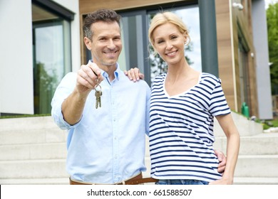 Close-up shot of happy couple standing in the garden and holding a key after moving their new modern house.