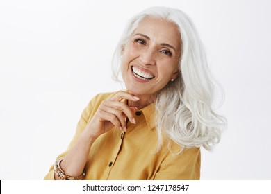 Close-up shot of happy delighted and accomplished charming european elderly female with white hair in yellow trench coat touching face gently laughing from joy feeling pretty and energized