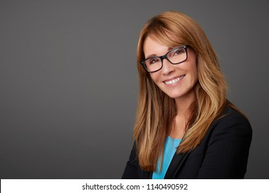 Close-up shot of a happy mature businesswoman looking at camera and standing at isolated background.
