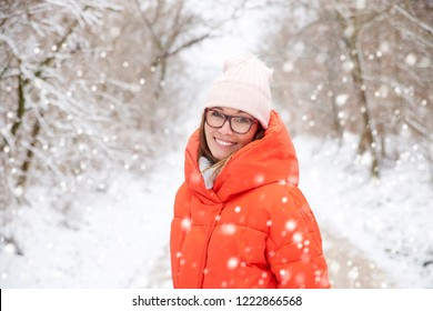 Close-up shot of a happy middle aged woman wearing hat while standing outdoor and enjoy snowfall.
