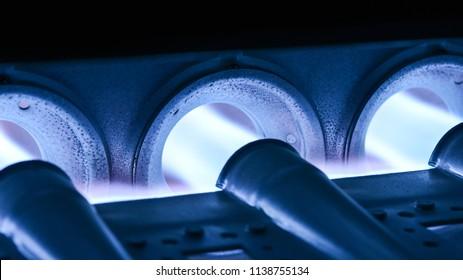 Closeup Shot Of Home Furnace Burner Ignited With Crimson Blue Flame