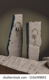 Close-up shot of hoop earrings fixed on the gray half-sawn stones on the sage green background. Each earring is made as a golden ring with white nacre discs and a golden twig with crystal beads.