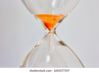 Close-up shot of an hour-glass with orange sand illustrating time running out.