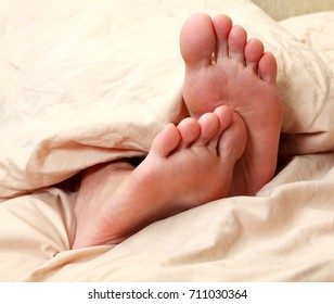 Closeup shot of human adult feet under the white blanket