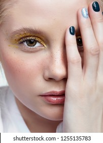 Closeup shot of  human female face. Woman with unusual glitter glitzy vogue face beauty makeup. Girl with yellow smoky eyes eye shadows and hand near face