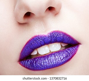 Closeup shot of human female face. Woman with violet lips makeup and white dentes.