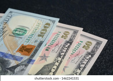 A closeup shot of a hundred and two fifteen united states dollars on a dark gray background