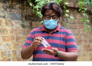 A closeup shot of an Indian man with a mask and glasses on the brickwall background