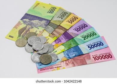 Closeup shot of Indonesia Rupiah banknotes and coins in white background.