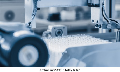 Close-up Shot of the Industrial Manufacturing Medical Test Tubes, Sorting and Packaging Process. Sterile High Precision Factory Machinery Producing Items for Medical Use. Abstract Industrial Concept.