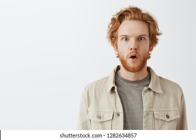 Close-up shot of interested and impressed handsome amazed redhead guy with beard in jacket over t-shirt folding lips in wow and popping eyes gazing at incredible intriguing offer over gray wall