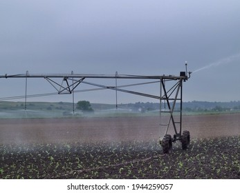 A closeup shot of the irrigation piping system watering farm cropland on the sky background