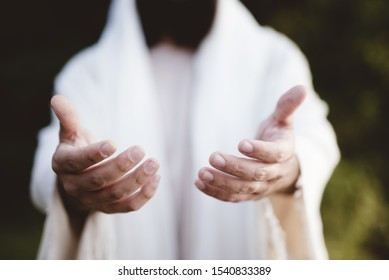 A closeup shot of Jesus Christ reaching out with a blurred background
