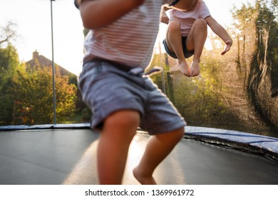 Closeup shot of kids jumping high on a trampoline