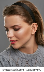 Closeup shot of a lady with coral pink lipstick and brown smokey eyes. The woman with slight smile is wearing jumper and black matte headband. The lady is posing on a gray background, looking down.